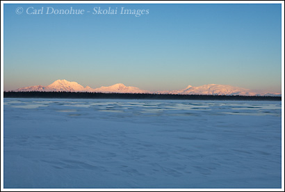 The Wrangell Mountains, including Mt Drum, Mt Sanford, Mt Zanetti and Mt Wrangell, from Willow Lake, frozen over and ice covered in winter, Wrangell - St. Elias National Park, Alaska.