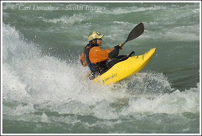 A whitewater kayaker surfing on a play wave on the Rio Baker or Baker River, Patagonia, Chile.