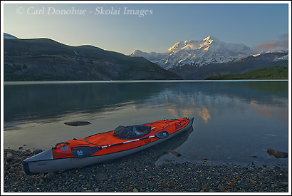 Sea kayak on the shore of Taan Fjord, Icy Bay, at sunset, with Mt. St. Elias, Wrangell St. Elias National Park, Alaska.