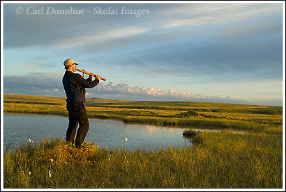 Hiker playing a traditional Native American Indian Flute on the coastal plain of ANWR, Alaska
