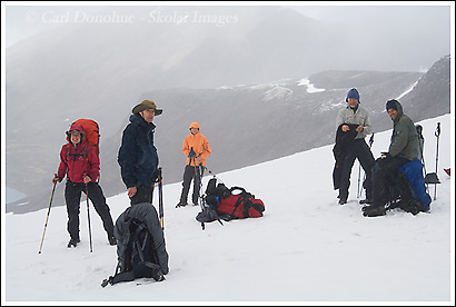 Backpackers stop in a snowy pass, near Bremner Mines, Wrangell St. Elias National Park, Alaska.