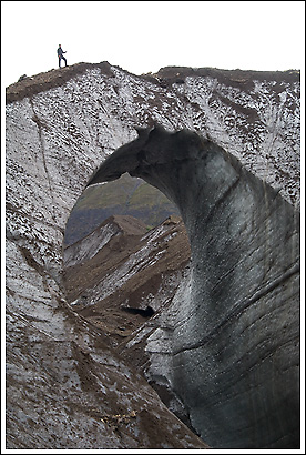 photo of a hiker atop an ice arch on the Sanford Glacier, Wrangell - St. Elias National Park, Alaska.