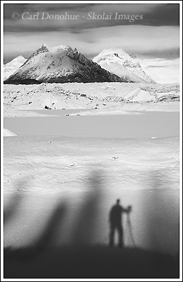 A black and white photo of a winter photographer and tripod standing before Kennicott Glacier, Donoho Peak, Wrangell - St. Elias National Park, Alaska.