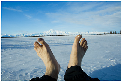 Hiker, barefoot, in winter, frozen lake, Mt. Sanford, Wrangell - St. Elias National Park, Alaska.