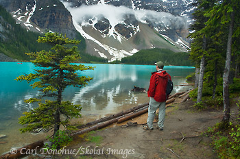 Tourist watching people canoeing on Moraine Lake, Banff, Canada.