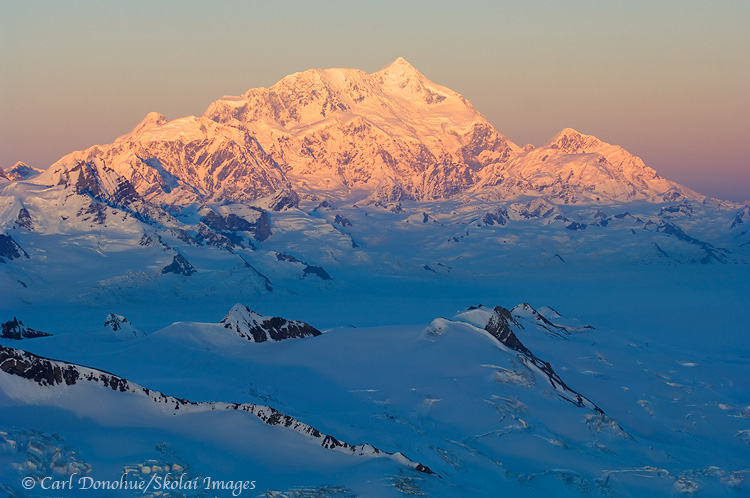 Mount Saint Elias, 18 008' high,catches the last of the sun's rays for the day, Wrangell-St. Elias National Park and Preserve, Alaska - aerial photo.