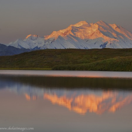 """Denali"", officially known as Mt. McKinley, the highest peak in North America, stands above the Alaska Range, a small kettle pond returning a perfect reflection. Denali National Park, Alaska."