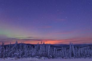 Northern lights and sunset over winter Alaska.