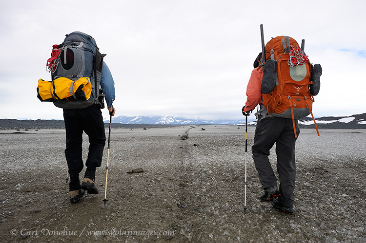 Two backpackers hiking across the Malaspina Glacier, alongside a medial moraine, Wrangell - St. Elias National Park and Preserve, Alaska.