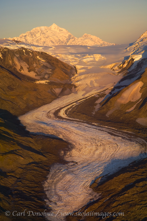 Mount Saint Elias, 18 008' high, stands tall in the evening light over an unnamed glacier, Wrangell-St. Elias National Park, Alaska - aerial photo.