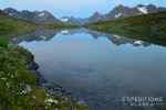 Beautiful alpine lake and reflection of the Chugach Mountains on a backpacking trip in Wrangell St. Elias National Park, Alaska.