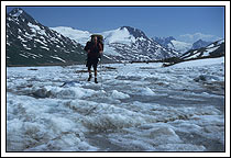 a hiker traverses an unnamed glacier in the Chugach Mountains, near Iceberg lake, Wrangell - St. Elias National Park, Alaska