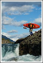 Whitewater kayaker stands on a rock scouting his line, Baker River, Patagonia, Chile
