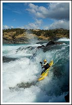 A whitewater kayaker paddles a narrow line over a waterfall, Baker River, patagonia, Chile.