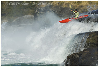 Whitewater kayaker dropping off a waterfall on the Baker River, Patagonia, Chile