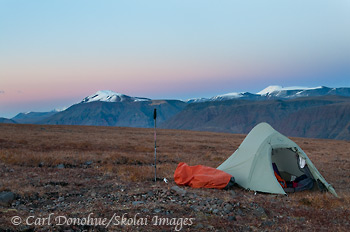 A backcountry campsite high on the tundra in the Wrangell Mountains. The high alpine ridges near Mt Jarvis, Wrangell - St. Elias National Park and Preserve provide a great place for hiking and backpacking. Sunset, Wrangell - St. Elias National Park and Preserve, Alaska.