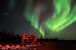 The welcome to the Dalton Highway road sign lit by a truck's taillights, glows under the northern lights in the sky. Aurora borealis photo, or northern lights, Alaska.