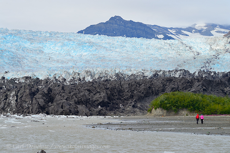 Two hikers walk beneath the Yahtse Glacier, a tidewater glacier calving into Icy Bay, Wrangell - St. Elias National Park and Preserve, Alaska.