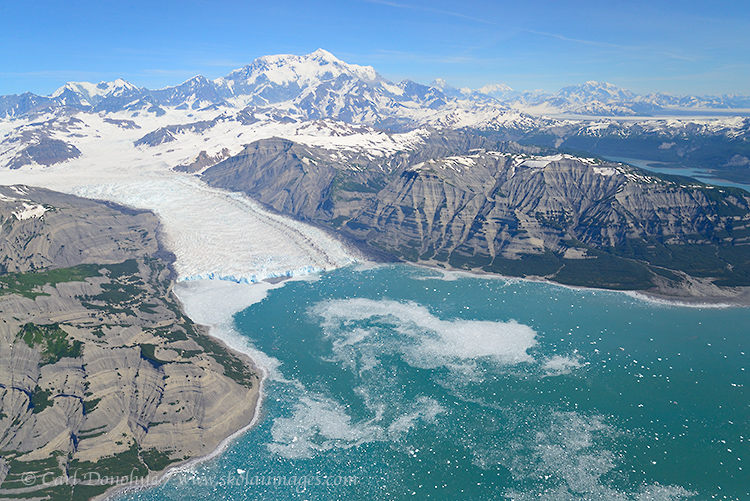 Ice calves off the Yahtse Glacier into Icy Bay, beneath the towering Mt. St. Elias. Wrangell - St. Elias National Park and Preserve, Alaska.