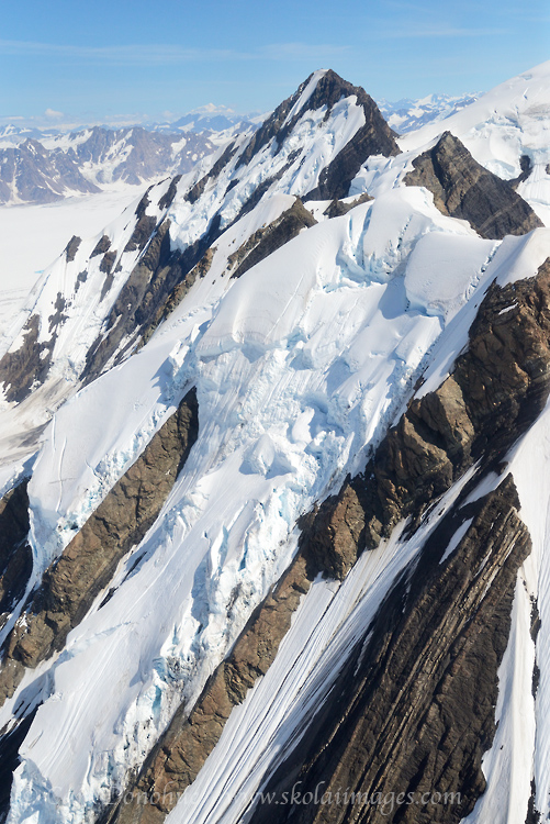 An aerial view of a broken glacier formed on the steep jagged crags of a mountain in the St. Elias Mountains Range. Wrangell - St. Elias National Park and Preserve, Alaska.