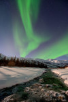A stock photo of the northern lights rising over a small creek, with the Brooks Range mountains in the background, part of Gates of the Arctic National Park and Preserve, Alaska.